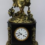 A 19th century French Ormolu & marble mantle clock, the surmount in the form of a figure dancing amongst vines, grapes and urns, the clock dial with Roman numerals on scrolling leaf capped feet, the movement inscribed E. Marlin & Co, striking on a bell, 67 cm high. Sold for £400 at Anthemion Auctions