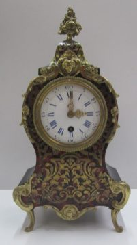 A 19th century French boulle work mantle clock with gilt floral finial, mask and scrolls on scrolling feet, the enamel dial with blue Roman numerals, marked to the movement, Brevete A Paris, 37 cms high. Sold for £210 at Anthemion Auctions
