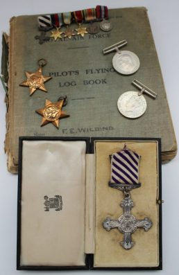 """Distinguished Flying Cross to Flying officer Frank E. Wilding, D.F.C, engraved 1944, together with the 1939-45 Star, The Burma Star, The Defence Medal, The War Medal, (missing the Air Crew Europe Star), with associated miniatures, The Royal Air Force Pilot's flying Log Book, newspaper cuttings and photograph album titled """"Round the world, by kind persuasion of the RAF"""", with photographs of those attached to the 136 Squadron and the aeroplanes and destinations. Provenance: by descent from the family. Sold for £3,750 at Anthemion Auctions"""