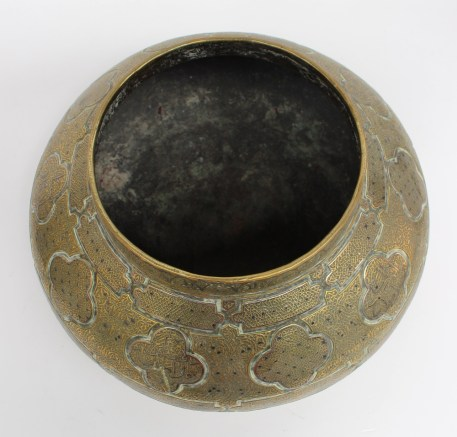 A Cairo ware brass bowl of squat form with panelled decoration of scrolls and lines, 36cm diameter. Sold for £920 at Anthemion Auctions