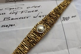An 18ct yellow gold ladies Bulova wristwatch, with a tapering log effect strap, the circular silvered dial with batons, No. 254741. Sold for £900 at Anthemion Auctions