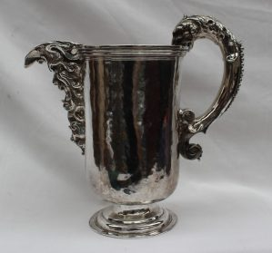 A continental white metal jug cast with a mask, scrolls and leaves, the handle cast with a leopards head, the hammered body on a spreading foot, marked NTO DOMI, 21cm high approximately 750 grams. Sold for £8,000 at Anthemion Auctions