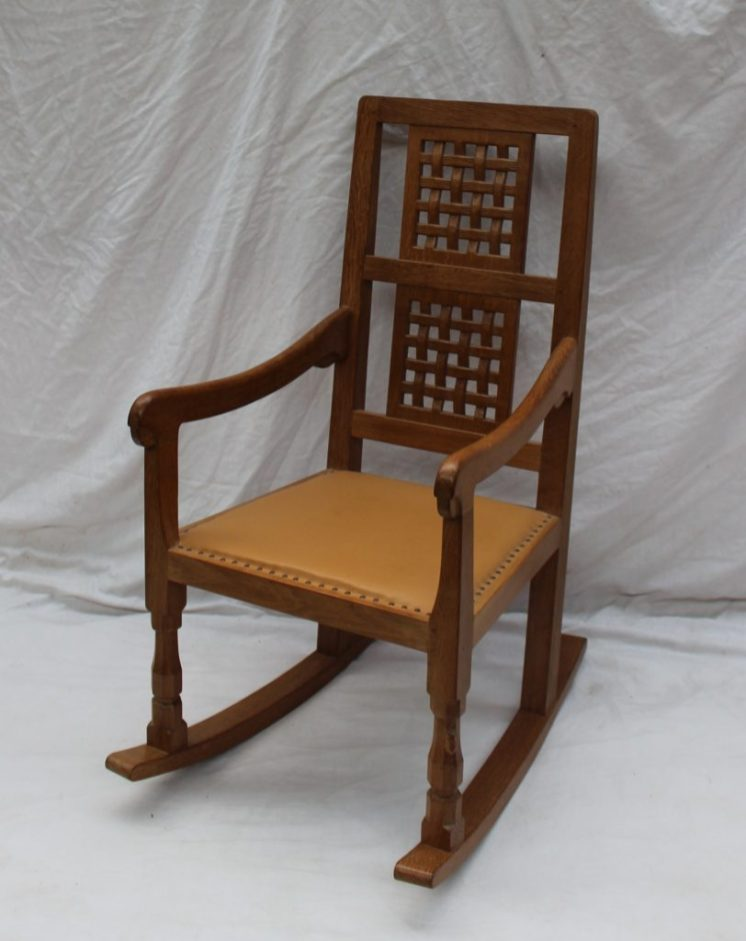 "A Robert Thompson of Kilburn ""Mouseman"" oak rocking chair with a double lattice back and tan leather seat, with original receipt dated 1989. Sold for £700 at Anthemion Auctions"