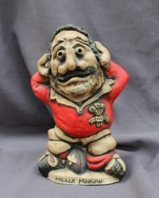 """A John Hughes pottery Grogg titled """"Mauler Morgan"""", in a Welsh jersey with his arms behind his head, the number 2 on his shirt, signed to the reverse, 26cm high. Sold for £120 at Anthemion Auctions"""