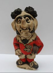 """A John Hughes pottery Grogg titled """"Pushover Pugh"""", in a red Welsh jersey with the No.3 on the reverse, signed to the base, 32.5cm high. Sold for £150 at Anthemion Auctions"""