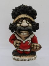 "A John Hughes pottery Grogg of a rugby player in a Welsh jersey with No.1 on the reverse, inscribed ""Wales Triple Crown 1976-79"", signed and dated 1979 to the base, 19.5cm high. Sold for £75 at Anthemion Auctions"
