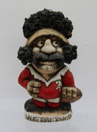 """A John Hughes pottery Grogg of a rugby player in a Welsh jersey with No.1 on the reverse, inscribed """"Wales Triple Crown 1976-79"""", signed and dated 1979 to the base, 19.5cm high. Sold for £75 at Anthemion Auctions"""