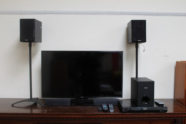 A Samsung model UE40JU6400K UHD flatscreen television, together with a Phillips Soundbar speaker HTL2160, subwoofer, Panasonic DMR-EX83 DVD recorder and Panasonic speakers on stands, (Sold as seen, untested)