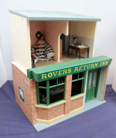 "Lot 642 - Estimates: £50 - 80. Dolls House - ""Rovers Return Inn"" fitted out as bar with figures, piano etc, together with a house interior"