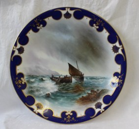 A Royal Worcester porcelain plate painted to the centre with fishing boats coming into shore on a choppy sea in a scrolling royal blue border, signed by Harry Davis, green mark and date code for 1902, 23cms diameter. Sold for £150 at Anthemion Auctions