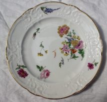 22nd August - Welsh Ceramics Lot 256. A pair of Nantgarw porcelain plates, with moulded C-scroll borders, both painted with scattered floral sprays and sprigs, gilt line rims, 24.5cm diameter, impressed NANT-GARW CW, Cashmore labels