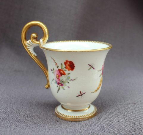 22nd August - Welsh Ceramics Lot 253. A Swansea porcelain miniature cup, of urn shape with a scrolling handle and pedestal foot, painted with sprays of garden flowers, 7cm high, 5cm diameter