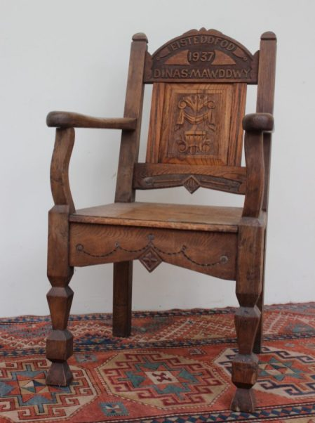 """An early 20th century Eisteddfod chair, the arched back carved for """"Dinas Mawddwy Eisteddfd 1937"""" the central panel carved with a vase of flowers, with a planked seat on square tapering legs, 108.5cm high. Sold for £360 at Anthemion Auctions"""