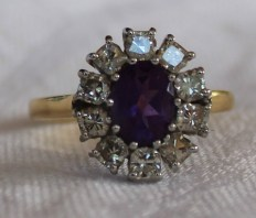 An amethyst and diamond ring, the oval faceted amethyst surrounded by ten princess cut diamonds to a white metal claw setting and 18ct yellow gold shank. Sold for £280 at Anthemion Auctions