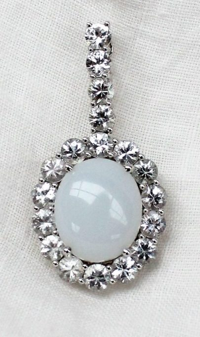22nd August Fine Sale - Jewellery Lot 105. A white sapphire and opaline pendant, set with eighteen round brilliant cut white sapphires to an 18ct white gold setting