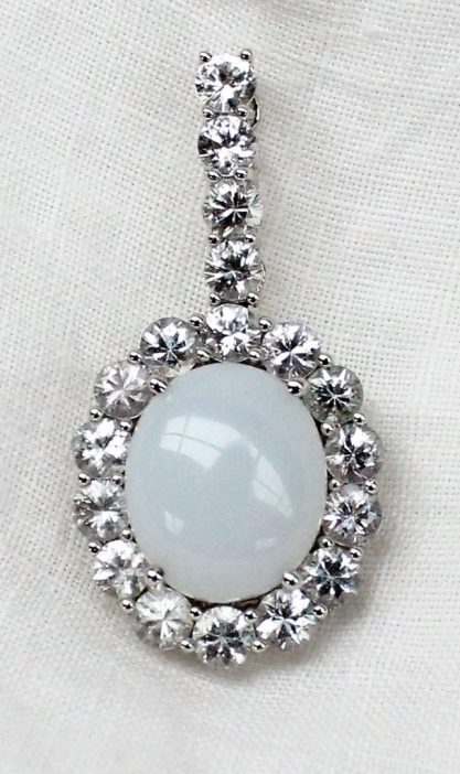 A white sapphire and opaline pendant, set with eighteen round brilliant cut white sapphires to an 18ct white gold setting. Sold for £170 at Anthemion Auctions