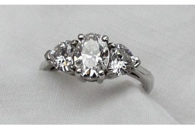 A three stone diamond ring, the central oval brilliant measuring 8.20 x 5.85 x 3.69mm totalling 1.13 carat, colour D, VS2, flanked by two heart shaped diamonds, one measuring 4.91 x 5.75 x 3.23mm, totalling 0.51 carat, Colour D, VS1, the other measuring 4.80 x 5.65 x 3.21mm totalling 0.50 carat, Colour D, VVS2, with GIA reports, to a platinum claw setting and shank. Sold for £5,800 at Anthemion Auctions
