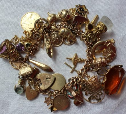 A 9ct yellow gold charm bracelet set with numerous charms including a canoe, tankard, key, elephant, half sovereign, cruise liner, flat iron hardstone revolving fob seal etc overall approximately 85 grams. Sold for £650 at Anthemion Auctions