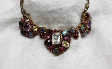 A Renaissance Revival gilt metal necklace, set with amethysts, sapphires, garnets, topaz and other semi precious stones to a closed back setting and scrolling links. Sold for £120 at Anthemion Auctions