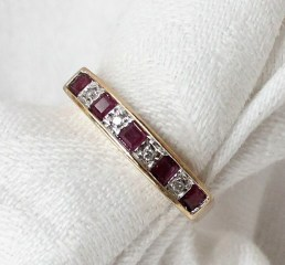 Lot 125A - A ruby and diamond half eternity ring set with five princess cut rubies and four round brilliant cut diamonds to a in 9ct yellow gold setting and shank