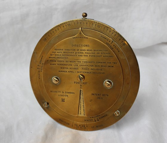 Lot 574A - A Negretti and Zambra desk top brass barometer dial with a fixed outer rim for Barometer readings, the two inner dials rotating for forecast predictions, Patent 6276, dated 1915, on an easel stand, 12cm diameter