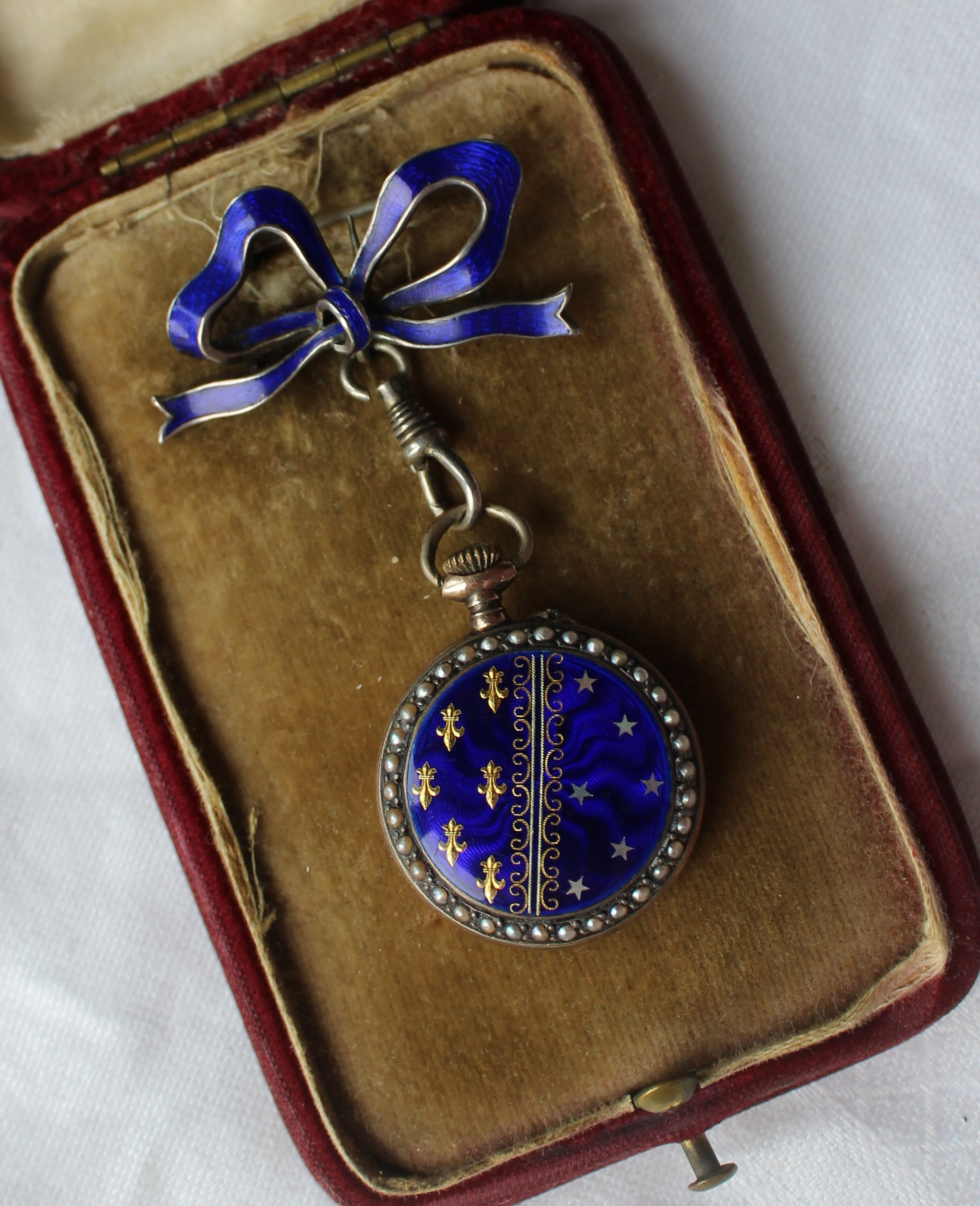 "Lot 107 - Estimates: £150 - 200 - A French white metal, enamel and seed pearl decorated fob watch, the enamel dial with Arabic numerals and pierced yellow metal hands, the bezel set with seed pearls. the back with blue enamel seed pearls, stars and fleur de lys, on a blue enamel bow suspension clasp, marked to the inside ""Fauvette Had., Argent Dore 0.935"""