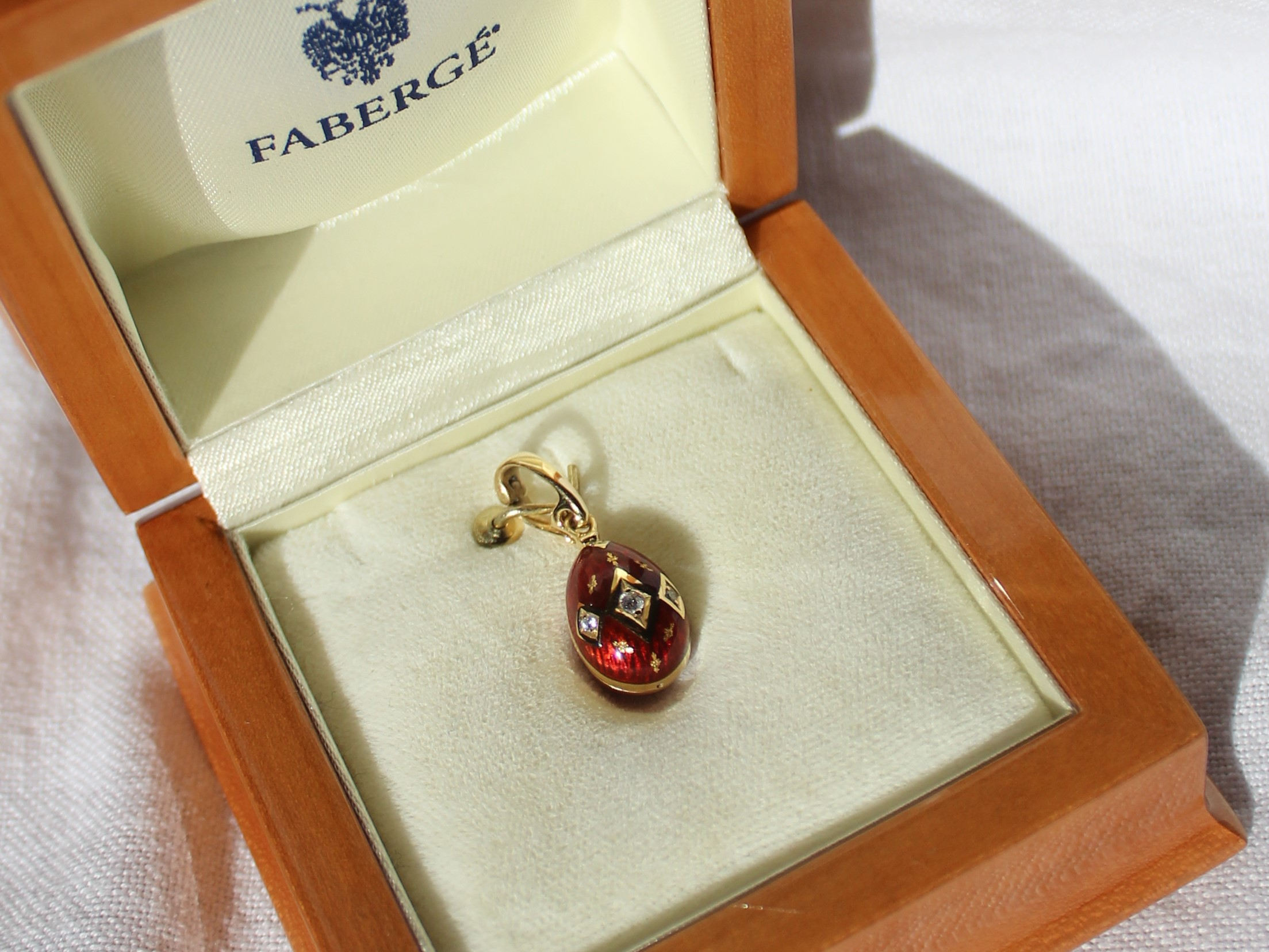 Lot 148 - Estimates: £300 - 500 - Victor Mayer for Faberge an 18ct gold, diamond and red enamel egg shaped pendant, set with three diamonds totally o.o6 of a carat, No.380/500, with certificate of authenticity and boxes
