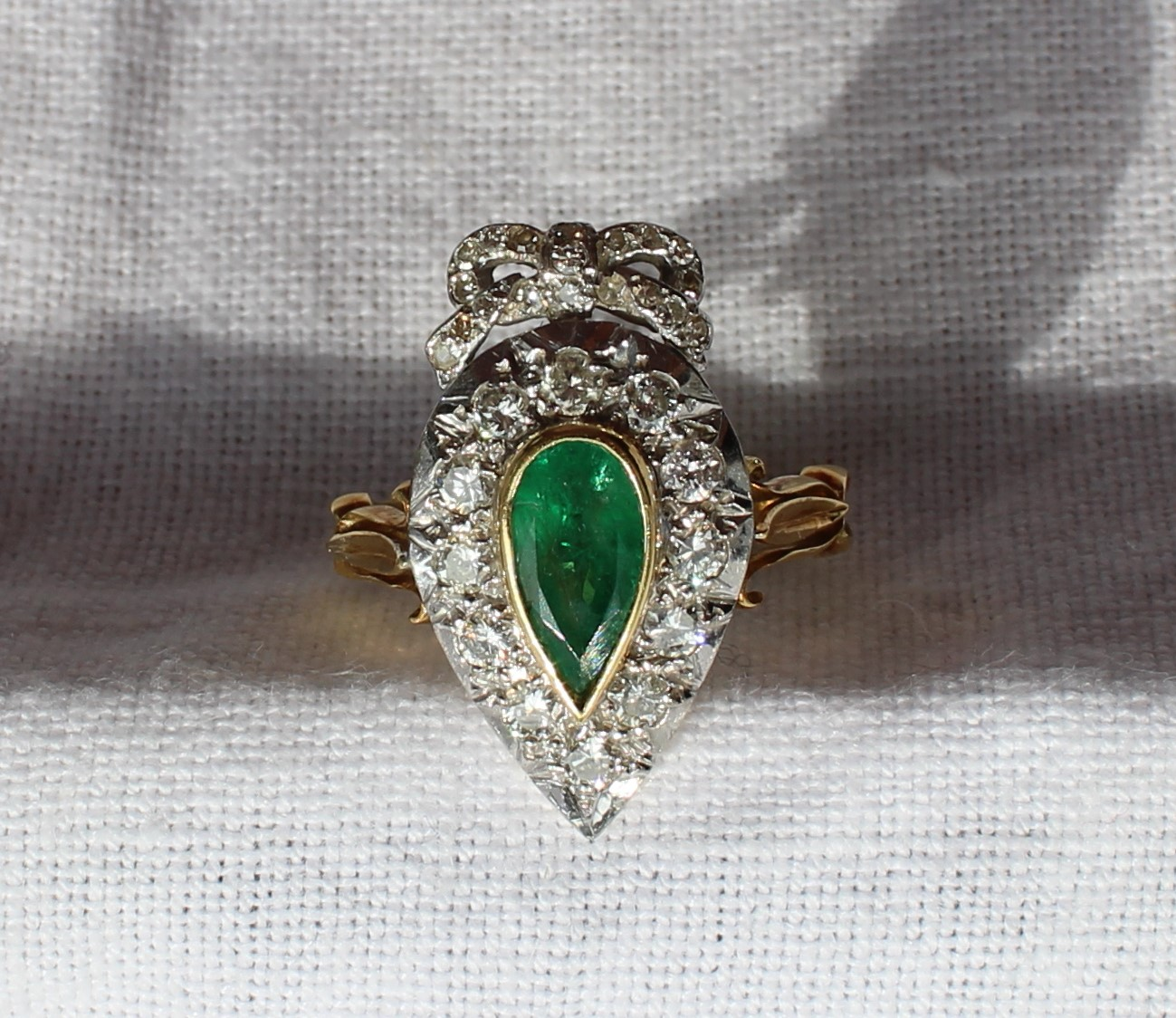 Lot 85 - Estimates: £300 - 400 - An emerald and diamond ring of heart shape, the pointed oval emerald approximately 10mm x 5mm surrounded by twelve round old cut diamonds with a diamond set bow cresting to a white metal setting and a yellow metal shank marked 18