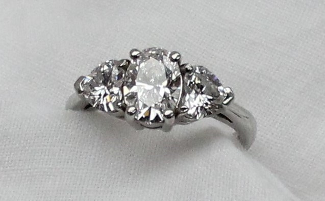 Sold for £5,800. A three stone diamond ring, the central oval brilliant measuring 8.20 x 5.85 x 3.69mm totalling 1.13 carat, colour D, VS2, flanked by two heart shaped diamonds, one measuring 4.91 x 5.75 x 3.23mm, totalling 0.51 carat, Colour D, VS1, the other measuring 4.80 x 5.65 x 3.21mm totalling 0.50 carat, Colour D, VVS2, with GIA reports, to a platinum claw setting and shank