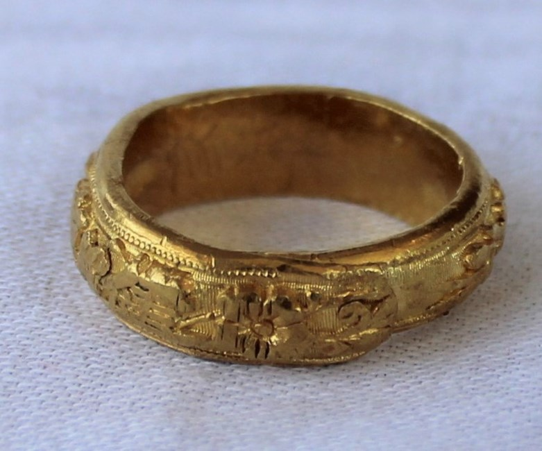 Sold for £570. A Chinese yellow metal ring, the edge decorated with Chinese characters and flowers possibly 24ct gold approximately 21 grams