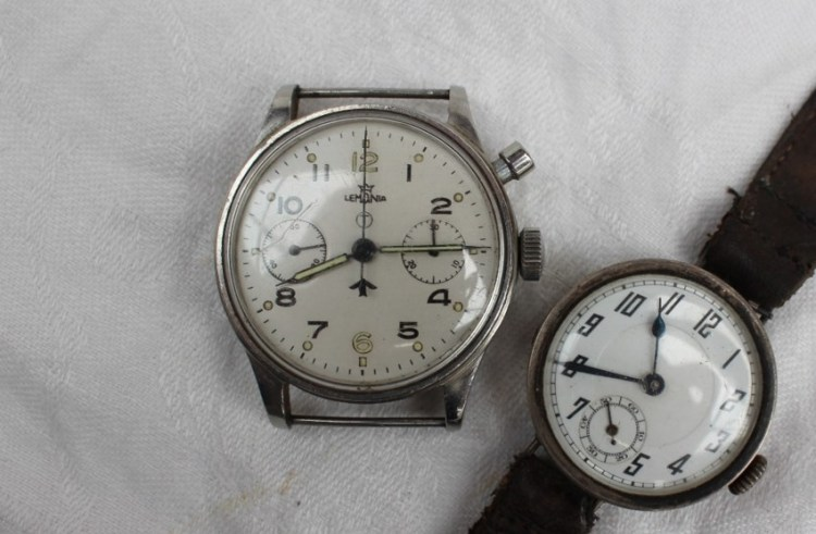 Sold for £1,650. A Gentleman's stainless steel British Military Lemania single button chronograph wristwatch with a white dial, Arabic numerals, signed, with a broad arrow and T in a circle, two dials for seconds and 30-minute register, luminous pencil hands, single button to operate chronograph, screw back with engraved military markings A.M/6B/551, 392/53, the movement numbered 667221, 38mm diameter, together with a continental silver mid size Gentleman's wristwatch with Arabic numerals and a seconds subsidiary dial on a leather strap