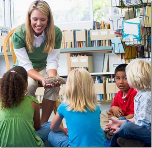 Kindergarten teacher and children looking at bird's nest in library