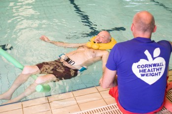 Partial abled man floating with aids in a swimming pool in Helston Cared for by Cornwall Healthy Weight