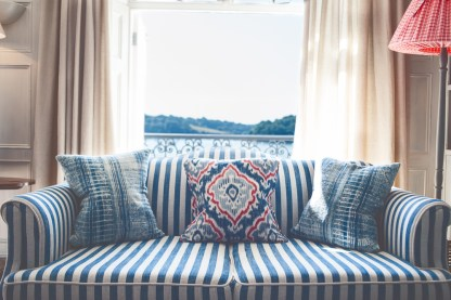 Striped sofa with cushions, behind is the St Mawes estuary