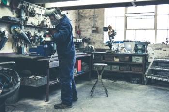 Engineer polishing Skinflints lights with an angle grinder