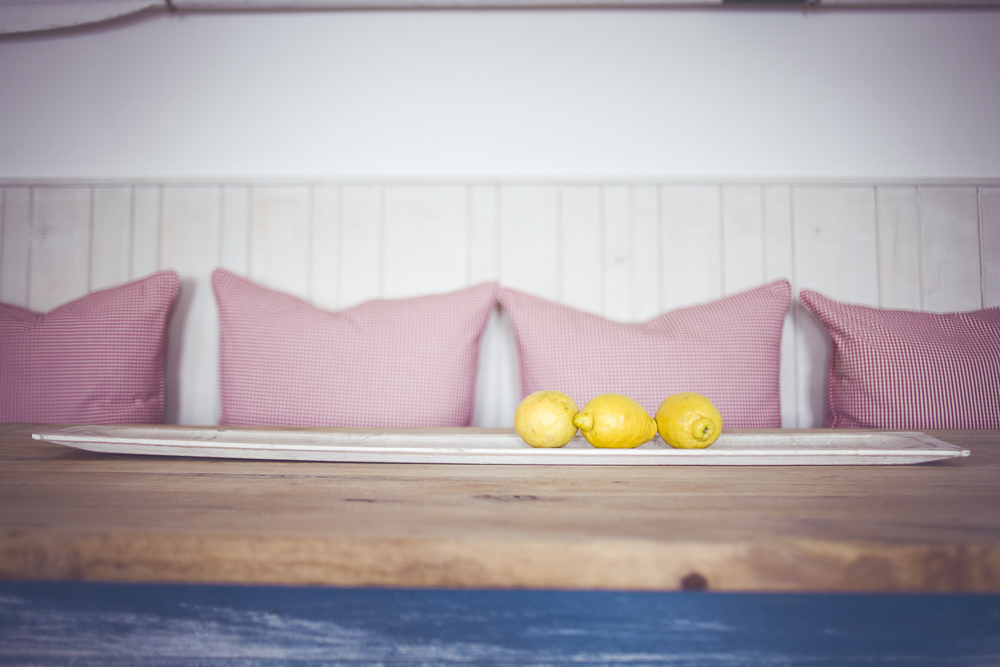 Three lemons on a table with red gingham cushions