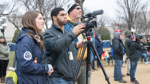Two students and Professor Rada record people watching the inauguration (Photo by Sophia Tulip)
