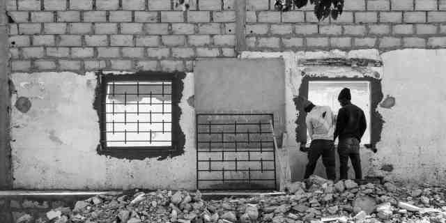 Black and white photo. A wall with two empty square holes where windows will be inserted. One has a large metal grate over it. The second grate leans up against the wall while two men prepare to mount it over the second window.