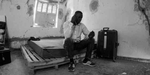 Black and white photo: A large Senegalese man wearing jeans, Adidas running shoes, and a nicely pressed white button-down shirt sits on the edge of a mattress. The mattress is on top of a short stack of wooden pallets. The house is under construction, so the walls are pitted and peeling with cement scars. The man holds a phone to his ear while a cable connects it to the mobile charger in his other hand.