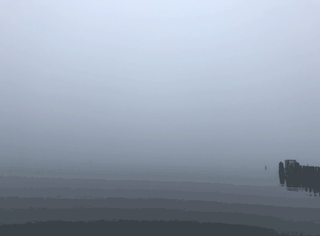 an image of a grey misty day where the ocean and sky appear as one matrix