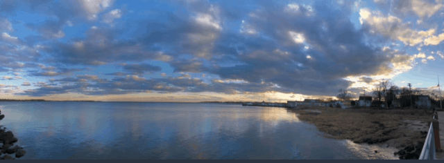 early dusk on Long Island Sound with clouds spread across a blue sky and the sun setting in the lower right hand corner of the image