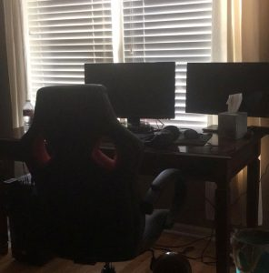 A computer desk with two large monitors and a gaming chair