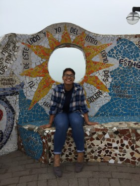 Melissa Anderson-Chavarria smiling in front of a mosaic wall
