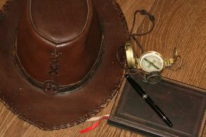 Brown hat with a compass and pen