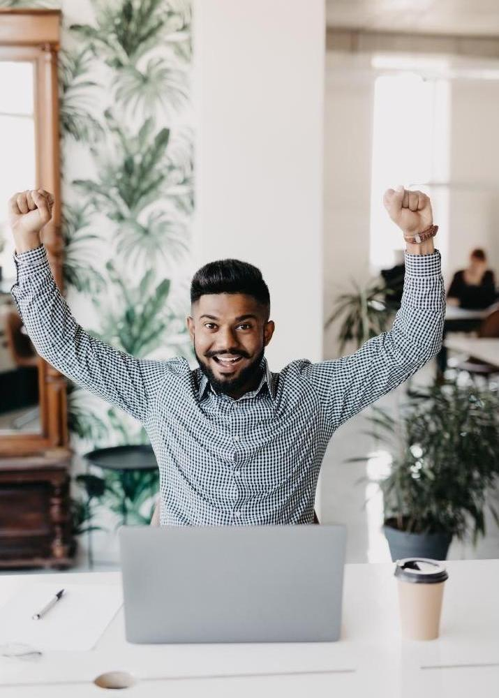 Man at a computer with fists raised in celebration