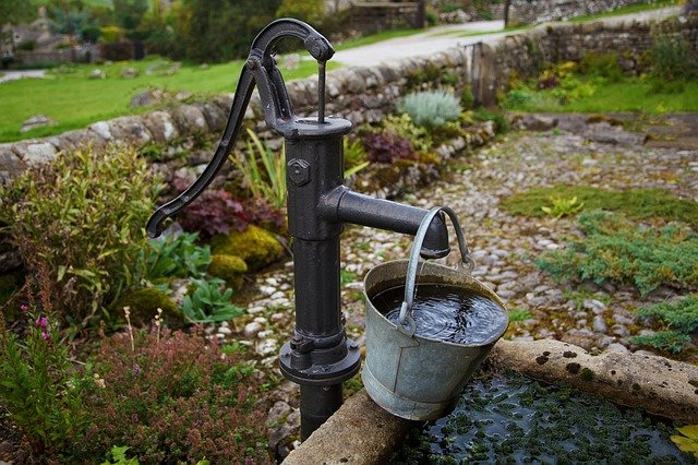 Political organization and disease. A metal water pump for a well with a metal bucket of water.