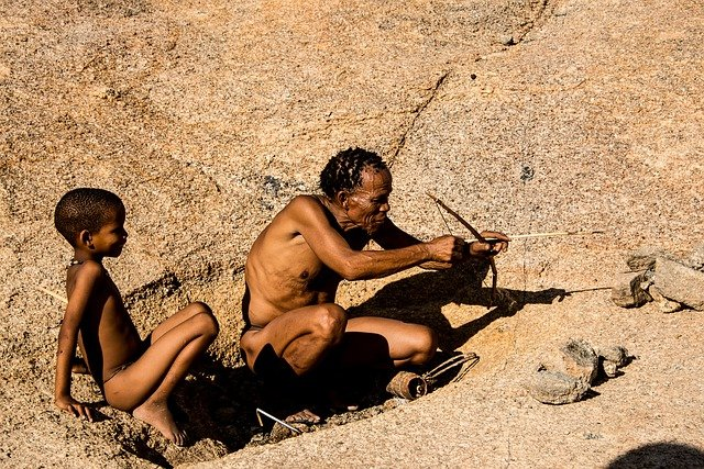 A to Z Terms in Cultural Anthropology. Indigenous African father showing son how to use a bow and arrow.