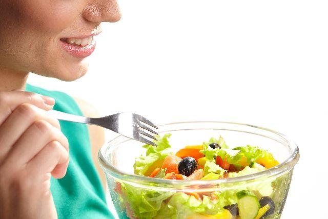 食物繊維が多い野菜を食べる女性の写真