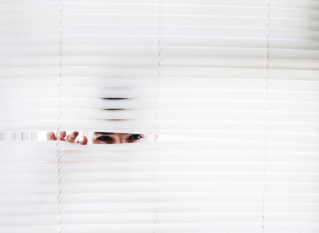 Man peeking through blinds with idle curiosity