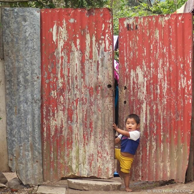 Rudy Giron: Antigua Guatemala &emdash; Boy opening a red lamina doorway around Antigua Guatemala